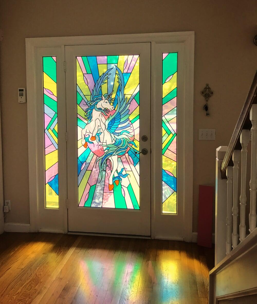 Glass design of vibrant unicorn in door entryway